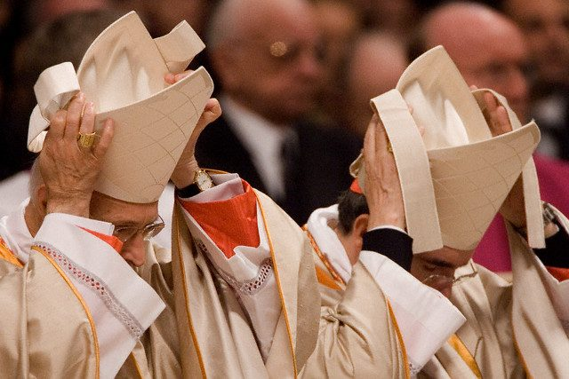 25 Nov 2007, Rome, Italy --- Newly-elected Cardinal Angelo Bagnasco (L) adjusts his cardinal skull during Pope Benedict XVI's second concistory ceremony, held in St. Peter's Basilica at the Vatican. The Pope elevated 23 new cardinals, including 18 eligible to take part in a papal election, being under 80. --- Image by © Alessandra Benedetti/Corbis